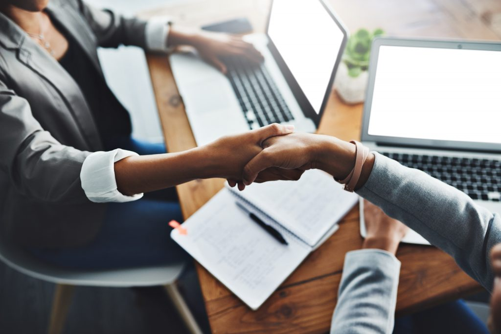 two businesswomen shaking hands in an office