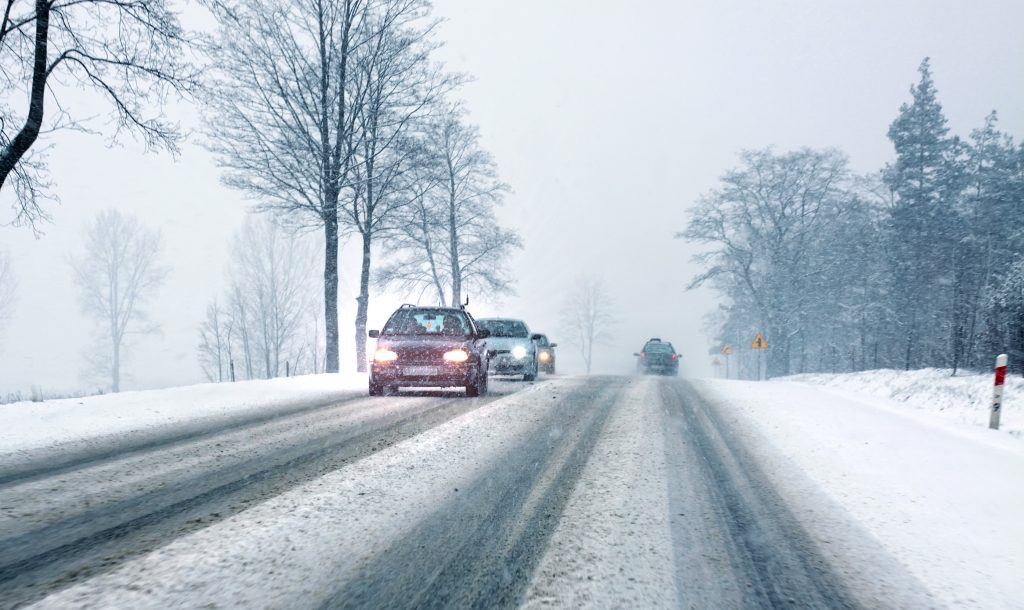 Cars on road in snowy weather conditions