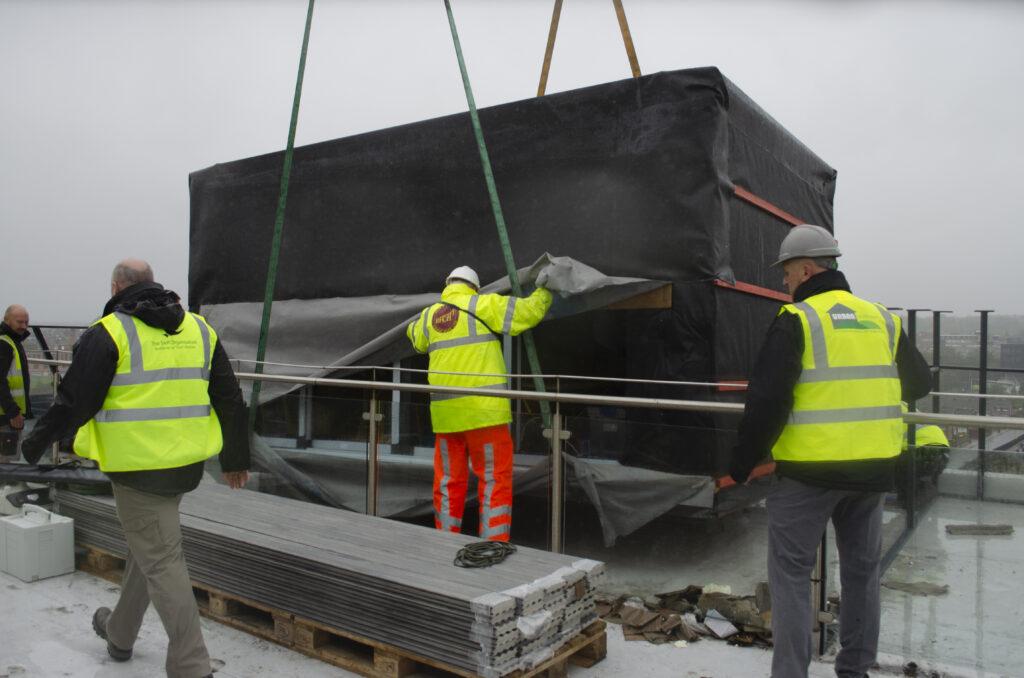 Crane lifting garden studio onto roof